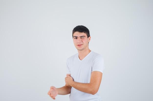 Junger mann, der ein auge schließt, während kamera in t-shirt betrachtet und lustig schaut. vorderansicht.
