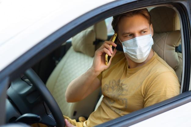 Junger mann, der ein auto fährt, das eine medizinische maske mit einem mobiltelefon trägt