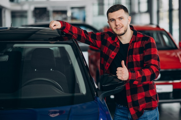 Junger mann, der ein auto in einem autohaus wählt