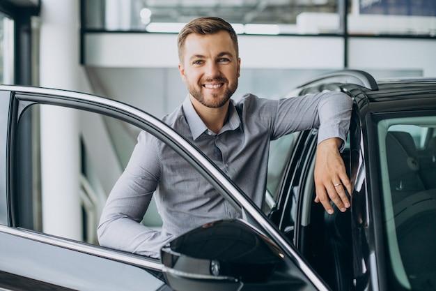 Junger mann, der ein auto in einem autosalon wählt
