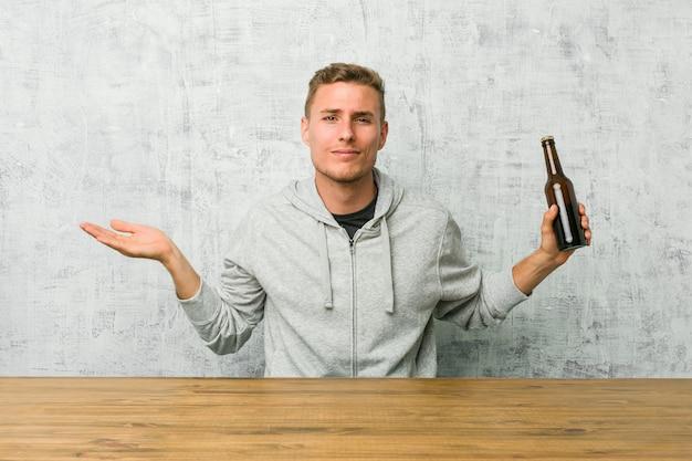 Junger mann, der ein bier auf einem tisch trinkt, der an fragenden gesten zweifelt und mit den schultern zuckt.