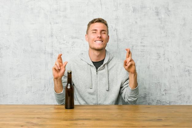 Junger mann, der ein bier auf einem tisch trinkt, der daumen drückt, um glück zu haben
