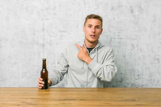 Junger mann, der ein bier auf einer tabelle zeigt auf die seite trinkt