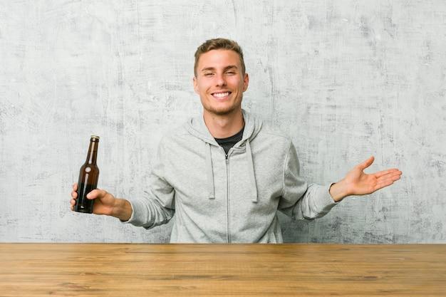 Junger mann, der ein bier auf einer tabelle zeigt einen willkommenen ausdruck trinkt.