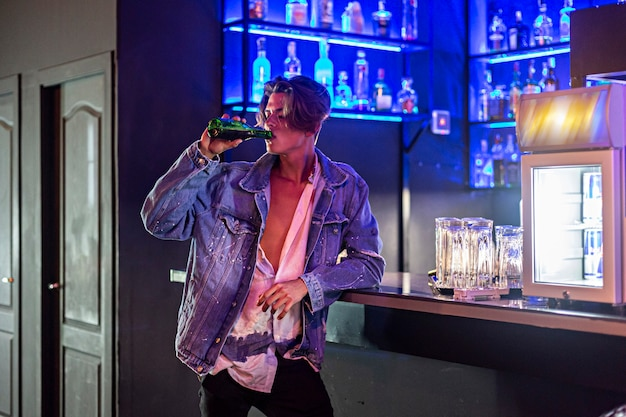 Junger mann, der ein bier in einer bar mit neonlichtern trinkt