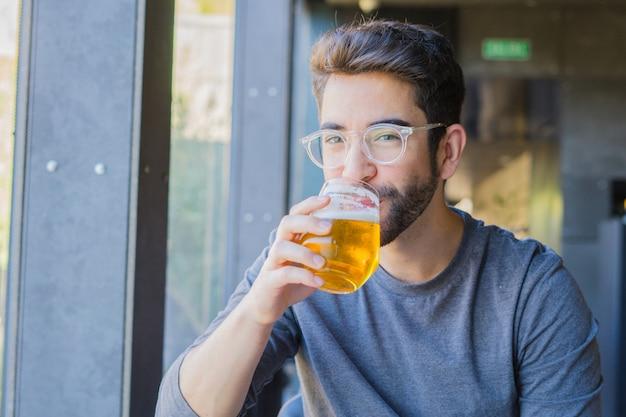 Junger mann, der ein bier trinkt
