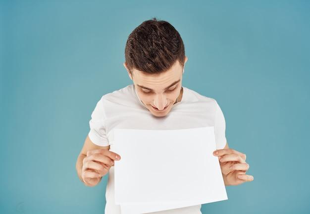 Junger mann, der ein blatt papier mit beiden händen hält
