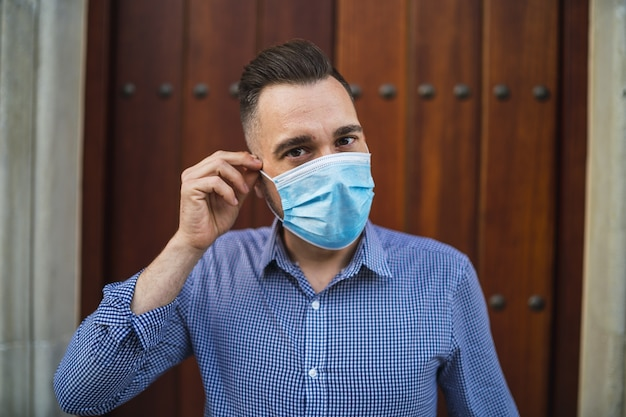 Junger mann, der ein blaues hemd trägt, das am tor mit einer medizinischen gesichtsmaske steht - covid-19-konzept
