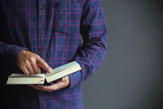Junger mann, der ein buch, kopienraum, abschluss oben öffnet und liest