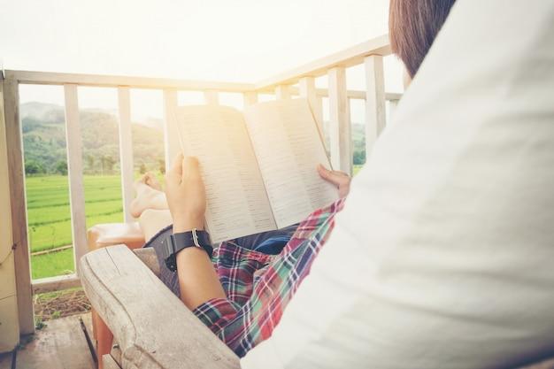 Junger mann, der ein buch liest im entspannenden bett an der terrasse mit grüner naturansicht liest.