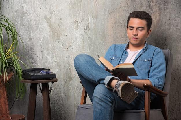 Junger mann, der ein buch liest und auf stuhl sitzt. hochwertiges foto