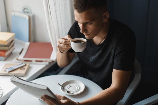Junger mann, der ein buch liest und kaffee in einem restaurant trinkt