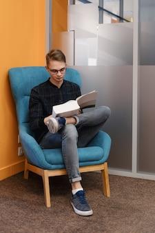 Junger mann, der ein dickes buch in einem sessel liest