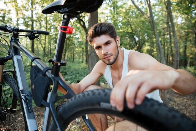 Junger mann, der ein fahrrad im wald repariert