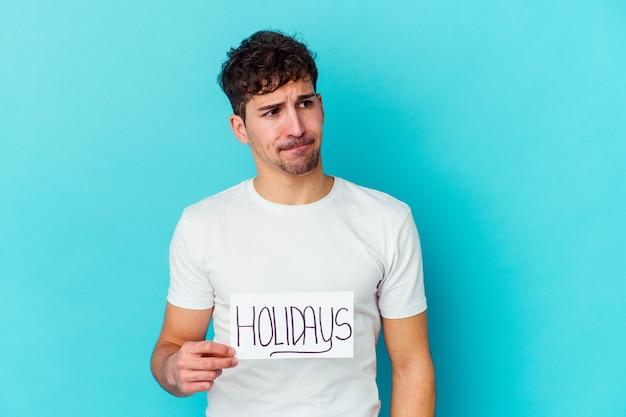 Junger mann, der ein feiertagsplakat isoliert hält, verwirrt, fühlt sich zweifelhaft und unsicher