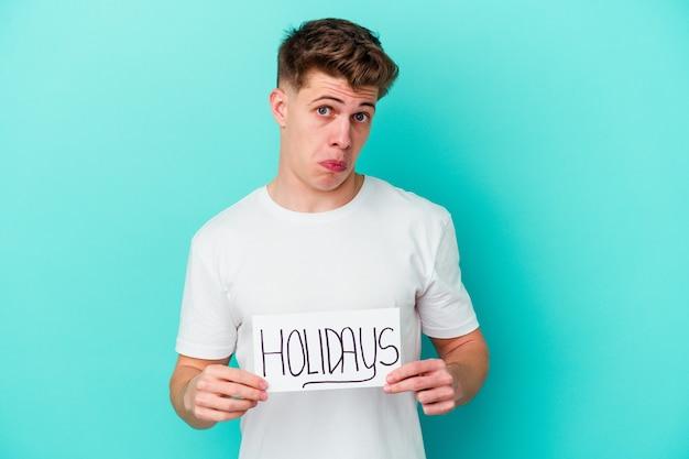 Junger mann, der ein feiertagsplakat lokalisiert auf blauer wand hält