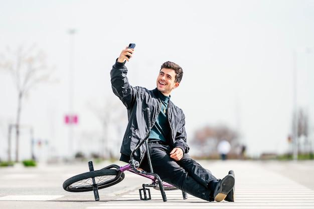 Junger mann, der ein foto mit smartphone mit seinem fahrrad macht