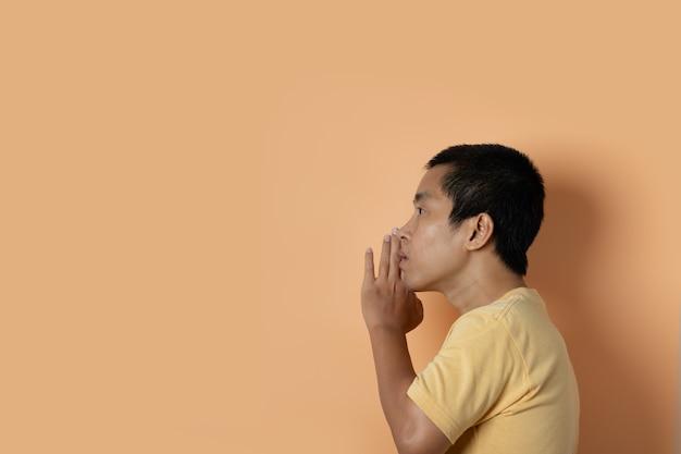 Junger mann, der ein geheimnis hinter der hand flüstert, die auf orange studiohintergrund lokalisiert wird. geheimnis, klatschkonzept.