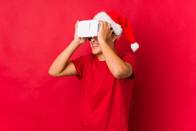 Junger mann, der ein geschenk am weihnachtstag hält