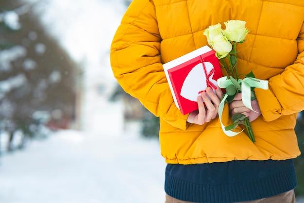 Junger mann, der ein geschenk und einen blumenstrauß von rosen, blumen, geschenkbox hinter seinem rücken hält. valentinstag urlaub
