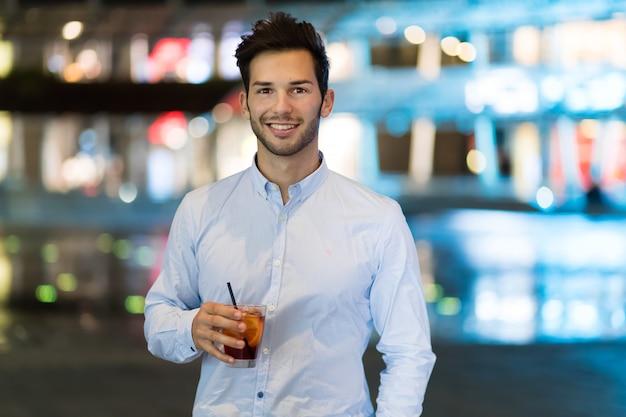 Junger mann, der ein getränk an einem nachtclub im freien hält