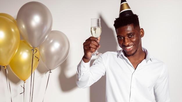 Junger mann, der ein glas champagner hält