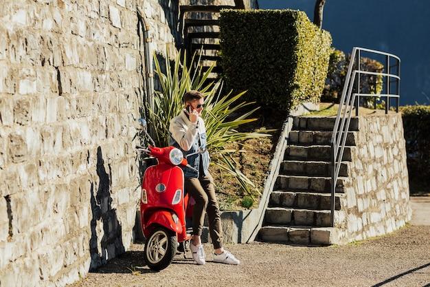 Junger mann, der ein handy auf dem roten motorrad hält.