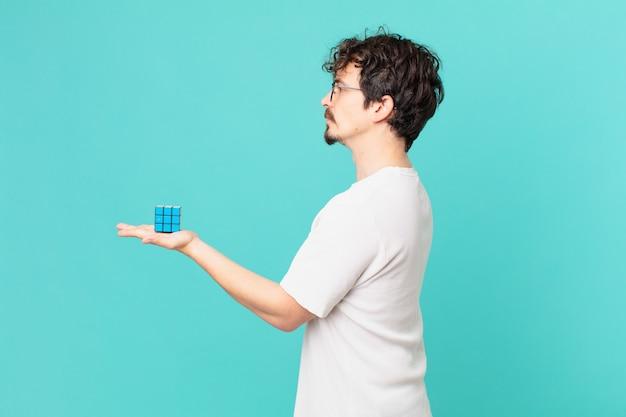 Junger mann, der ein intelligenzproblem in der profilansicht löst, denkt, sich vorstellt oder träumt