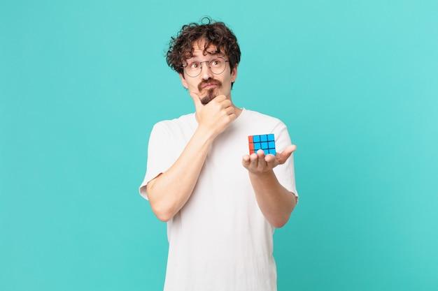 Junger mann, der ein intelligenzproblem löst, denkt, sich zweifelnd und verwirrt fühlt
