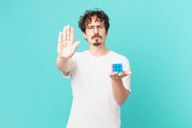 Junger mann, der ein intelligenzproblem löst, der ernst aussieht und eine offene handfläche zeigt, die eine stopp-geste macht