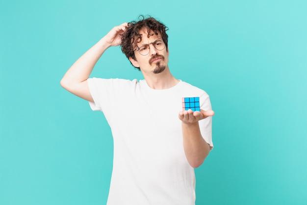 Junger mann, der ein intelligenzproblem löst, sich verwirrt und verwirrt fühlt und sich am kopf kratzt