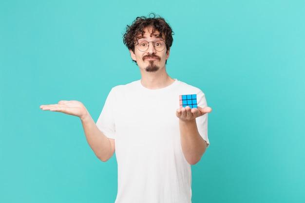Junger mann, der ein intelligenzproblem löst, sich verwirrt und verwirrt fühlt und zweifelt