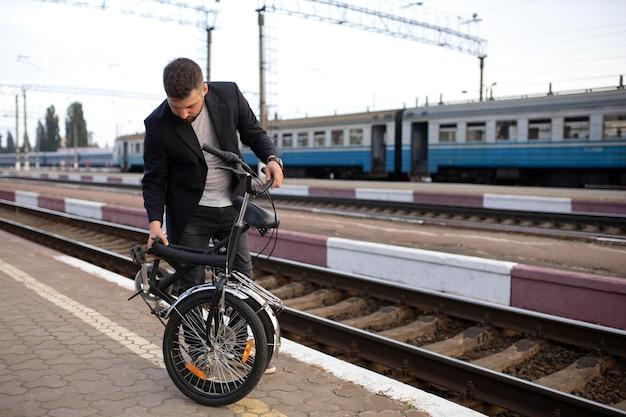 Junger mann, der ein klapprad benutzt, während er mit dem zug fährt