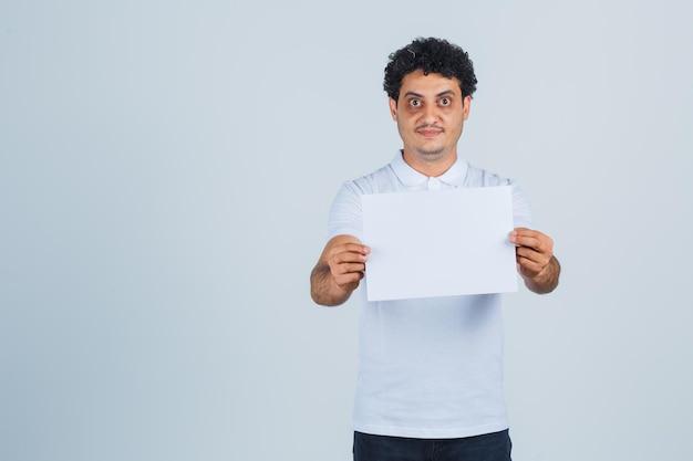 Junger mann, der ein leeres papierblatt im weißen t-shirt, in der hose hält und selbstbewusst aussieht, vorderansicht.