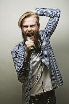 Junger mann, der ein mikrofon anhält