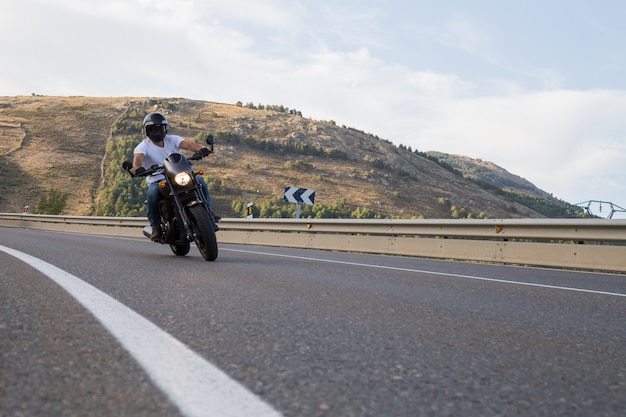 Junger mann, der ein motorrad auf der straße sich dreht in eine kurve in den bergen am sonnigen tag reitet.