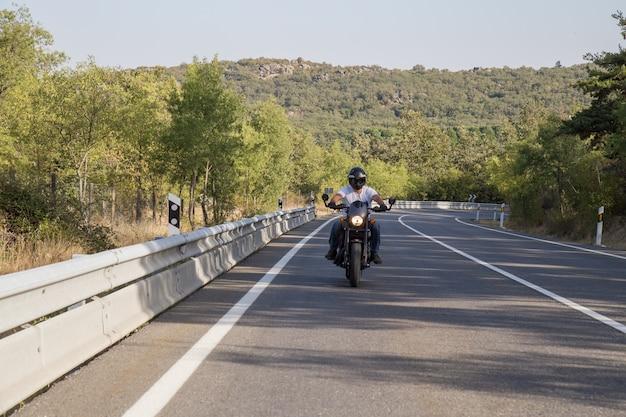 Junger mann, der ein motorrad auf straße in den bergen am sonnigen tag reitet.