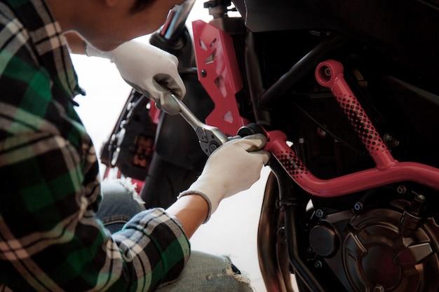 Junger mann, der ein motorrad repariert.