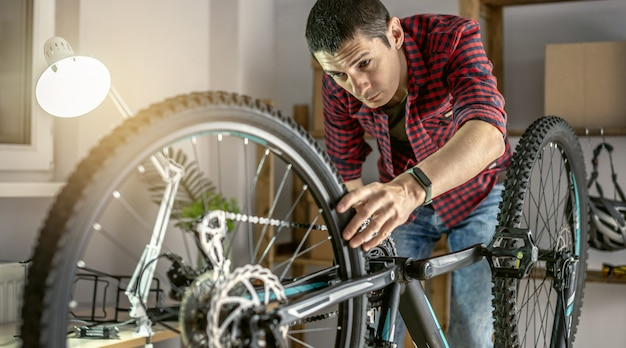 Junger mann, der ein mountainbike in einer werkstatt repariert. konzept der vorbereitung auf die neue saison, reparatur und wartung