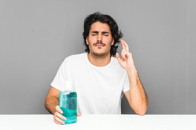 Junger mann, der ein mundwasser hält, das finger kreuzt, um glück zu haben