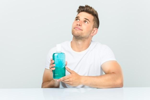 Junger mann, der ein mundwasser hält, das mit zweifelhaftem und skeptischem ausdruck seitwärts schaut.