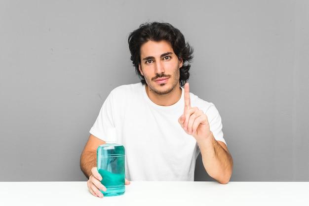 Junger mann, der ein mundwasser hält, das nummer eins mit finger zeigt.