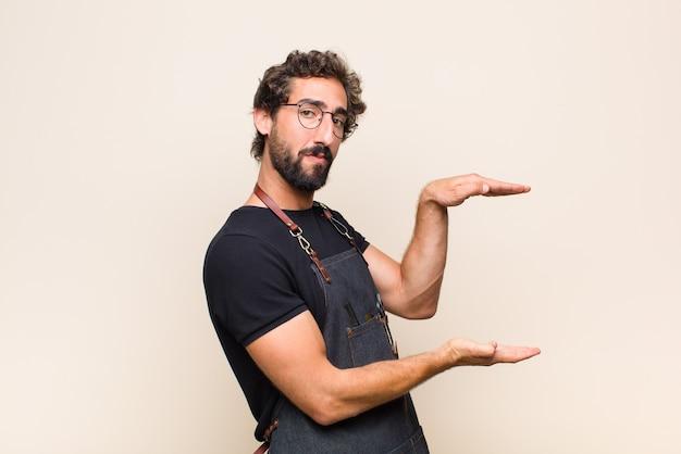 Junger mann, der ein objekt mit beiden händen auf seitenkopierraum hält, ein objekt zeigt, anbietet oder wirbt