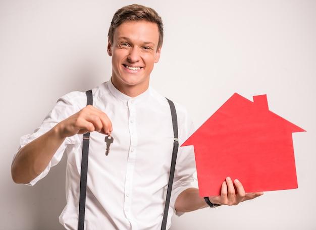 Junger mann, der ein papierhaus hält