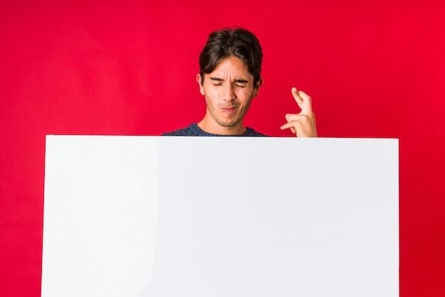 Junger mann, der ein plakat hält, das finger kreuzt, um glück zu haben
