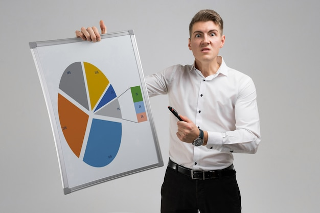 Junger mann, der ein plakat mit einem diagramm lokalisiert auf einem hellen hintergrund hält