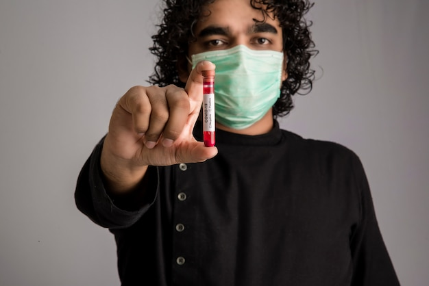Junger mann, der ein reagenzglas mit blutprobe für coronavirus- oder 2019-ncov-analyse hält.