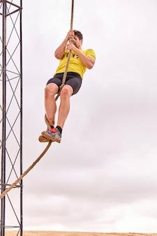 Junger mann, der ein seil von knoten in einem spartanischen rennen klettert