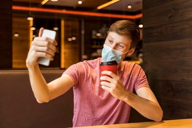 Junger mann, der ein selfie beim tragen einer gesichtsmaske in einem café nimmt