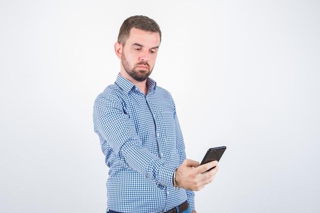 Junger mann, der ein selfie im hemd, in den jeans nimmt und ernst schaut, vorderansicht.
